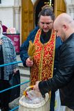 Priest consecrates Easter eggs and Easter cakes on the eve of Easter royalty free stock photo