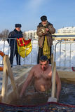 Priest consecrates the ice hole on Epiphany day. Russia Stock Photography