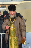 Priest consecrates the ice hole on Epiphany day. Russia Royalty Free Stock Images