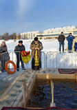 Priest consecrates the ice hole on Epiphany day. Russia Royalty Free Stock Photo