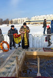 Priest consecrates the ice hole on Epiphany day. Russia Stock Image