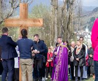 Priest with cross at calvary. RUZOMBEROK, SLOVAKIA - APRIL 14: Priest with cross at calvary. The Way of the cross during easter on April 14, 2019 in Ruzomberok stock photo