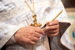 A priest with a cross holding extinguished candle wax Stock Photos