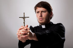 Priest with cross. Young christian priest is holding a cross royalty free stock image