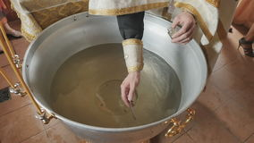 The priest crosses the water in font with brush before the ceremony of baptism stock video