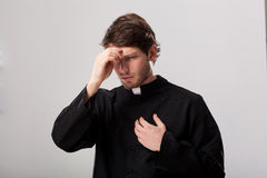 Priest crossing himself. Priest wearing a soutane begining his prayer Royalty Free Stock Photography