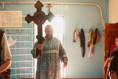 The priest enters the church. Russia. Tomsk. Priest getting on the hip a large wooden cross, enters in an orthodox church. Orthodox celebrations devoted to the Stock Photos