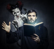 Priest evicting demons. Conceptual photo stock image
