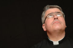 Priest gazing towards heaven. A portrait of a priest or minister wearing a white collar, looking upwards as if to look to heaven. Isolated on a black background stock photography