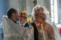 Priest gives wine to a crowned bride Royalty Free Stock Photography