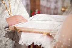 Priest giving Bible to bride Royalty Free Stock Photography