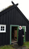 Priest at grass roofed church Stock Photos