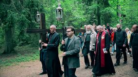 Priest and grey head man carry cross like Jesus Christ. Religious procession. VILNIUS, LITHUANIA - JUNE 02, 2017: Bishop and old grey head man carrying cross stock video
