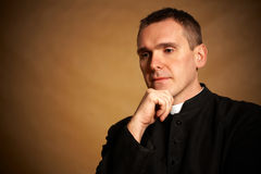 Priest with hand under chin Royalty Free Stock Images