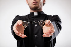 Priest handcuffed. Young christian priest in cassock arrested and handcuffed royalty free stock photos