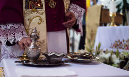 Priest hands. During baptism process Stock Photography