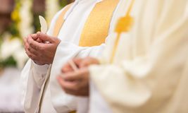 Priest` hands during a wedding ceremony/nuptial mass. Priest during a wedding ceremony/nuptial mass shallow DOF; color toned image Stock Image