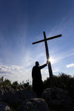 Priest hold a cross against the sun Royalty Free Stock Photography