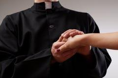 Priest holding believer hand. Good priest supporting believer and holding her hand stock images
