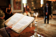 Priest holding bible in church. Hands of priest holding bible at alter inside church Stock Images