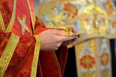 Priest holding bread and wine Royalty Free Stock Photography