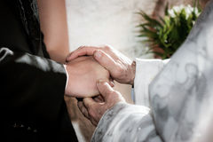 Priest holding hand blessing youg couple. At a wedding ceremony Royalty Free Stock Photo
