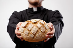 Priest holding loaf of bread Stock Photos