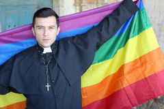 Priest holding the rainbow flag.  royalty free stock images