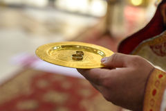 Priest holds plate with golden wedding rings Stock Photo