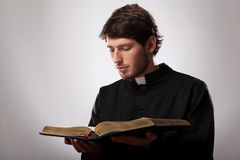 Priest with Holy Bible. Young christian priest is reading the Holy Bible Stock Photography
