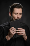 Priest kissing the Holy Bible. Portrait of priest kissing the Ho. Ly Bible against black background Royalty Free Stock Photo