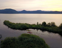 Priest Lake. Aerial view of Priest Lake in Idaho with two kayaks passing through, taken at sunset from a drone royalty free stock photography