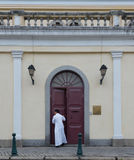 Priest leaving church in Macau China. Religion street photo of a father priest leaving a Portuguese church in Macau China Stock Images