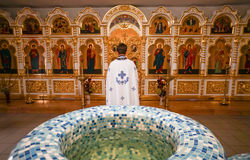 Priest looking to the icons. Cathedral, Kamyshin, Volgograd region., Russia, July 2017 Priest against the background of many icons, stands with his back to the royalty free stock photography