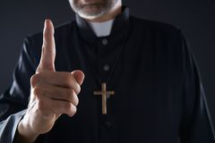 Priest male pointing finger up to heaven stock photo