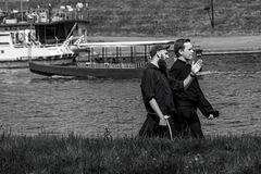 A Priest and a Monk walk by the Wisla River - Krakow 05 2018. Krakow is a city with a huge religious component where you can see priests and nuns going about stock image