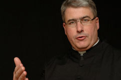 Priest with outstretched hand. A portrait of a priest of minister with a white clerical collar, reaching out with an outstretched hand stock photo