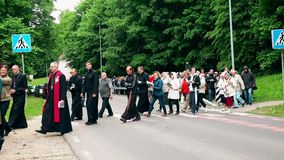 Priest people walk with religion cross Jesus pain Calvary. 4K. VILNIUS, LITHUANIA - JUNE 02, 2017: priest believing people procession walk in crowd carrying the stock video footage