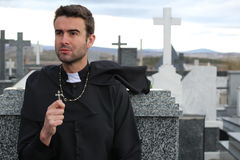 Priest performing an exorcism in a windy cemetery stock photos