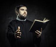Priest with Prayer book. Against dark background Stock Photos