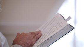 Priest praying with Bible book in church stock footage