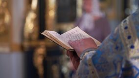 Priest praying with Bible book in church stock video
