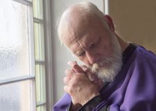 Priest praying in a church with a thoughtful expression. Mature priest praying in a church with a thoughtful expression royalty free stock image