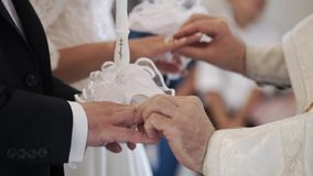 Priest praying in church at wedding ceremony and put on rings for newlyweds. Bride and groom stock footage