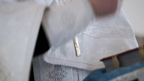 Priest praying with cross on chest in church stock footage