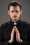 Priest praying to God. Portrait of priest praying while standing Stock Image