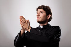 Priest is praying. Young christian priest is praying the rosary Royalty Free Stock Photography