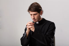 Priest is praying. Young christian priest is saying a prayer stock photo