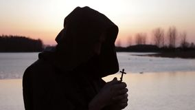 The priest prays, holds a cross in his hand stock video footage