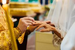Priest puts on ring on brides finger during church wedding ceremony. Exchange of rings. Horizontal view. Marriage concept stock photo